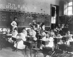 The teacher stands by in this late 19th century classroom, elementary students work on arithmetic.