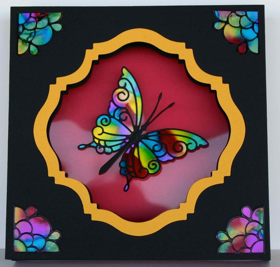 A three layer shadow box card with a Simon Says Stamp butterfly die on alcohol ink and Elizabeth Craft corners on alcohol ink. The frame is a Go Kreate die cut.