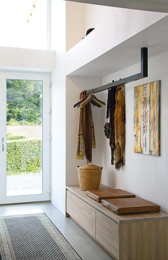 Efficient and practical mudroom entry space -- suspended coat rack in a modern shape and bold black hue,  built-in storage bench with the look of a chic credenza, added cognac leather seat pads for comfort and style, and a rustic saffron yellow oil painting to warm up the room with a bit of modern California style.