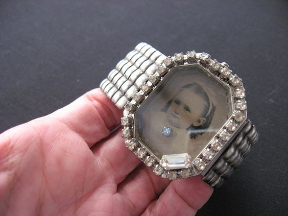 Repurposed from a big chunky watch.  I added the tintype of the pretty little girl and the rhinestones around the edge.