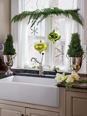 Bring the holiday cheer to your kitchen by adding rosemary plants, evergreen branches, and bold ornaments as decorative details.  #christmas #decorations