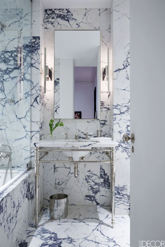 The bathroom vanity and tub are by Waterworks, the fittings are by Lefroy Books, and the sconces are by Ozone; the walls are sheathed in Calacatta Viola marble.