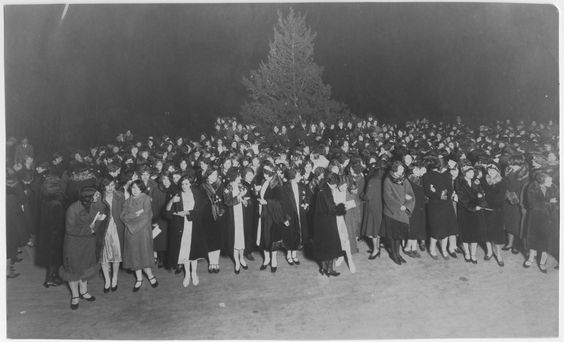 Students gathered around an outdoor Christmas tree in 1926.