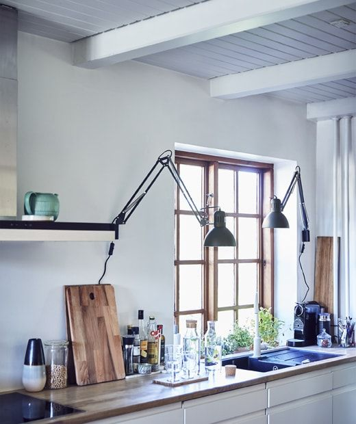 A White Kitchen With Two Work Lamps Installed On The Wall More At