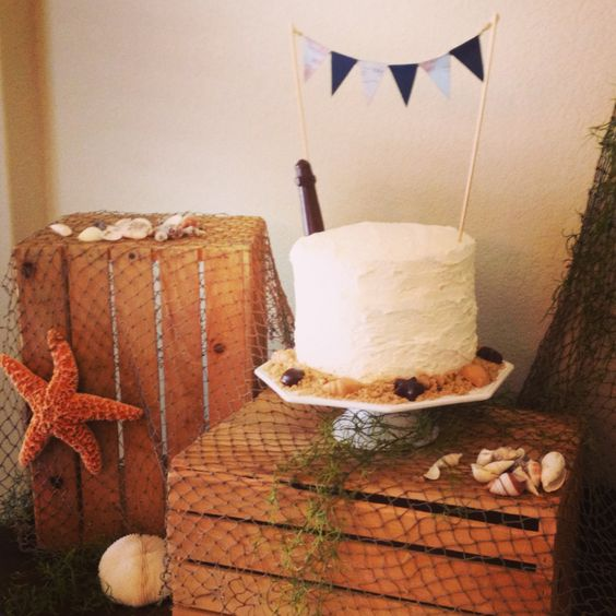 This four-layer chocolate cake with buttercream icing sits on top of some wooden crates that have been draped with a fishing net.  Faux seaweed, starfish and shells surround the cake and help to complete the nautical look. The cake is garnished with a chocolate lighthouse, chocolate shells, sand made from brown sugar and a pennate that matches the larger one hanging in the party space. Nautical birthday party. Event Planner and Photo by: One Event Design.