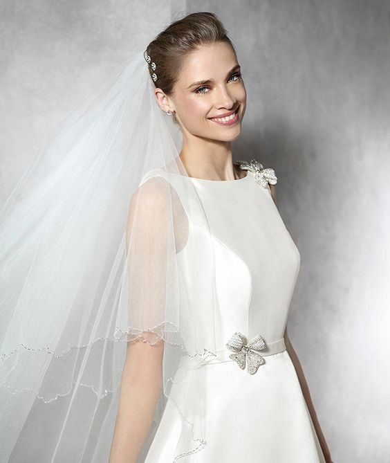 TELDE- Original, modern princess dress in mikado silk. Bateau neckline with gemstone embroidery appliqué on the shoulder. Cross-over neckline with sheer back. Mikado silk belt at the waist with a gemstone embroidery appliqué. Mikado silk skirt with pockets.