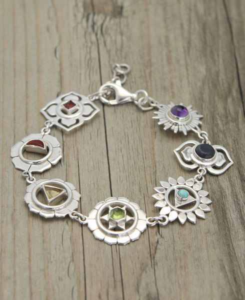 Sterling silver bracelet contains seven silver charms that correspond to the seven Chakras. Each charm is inlaid with a colorful semi-precious stone.