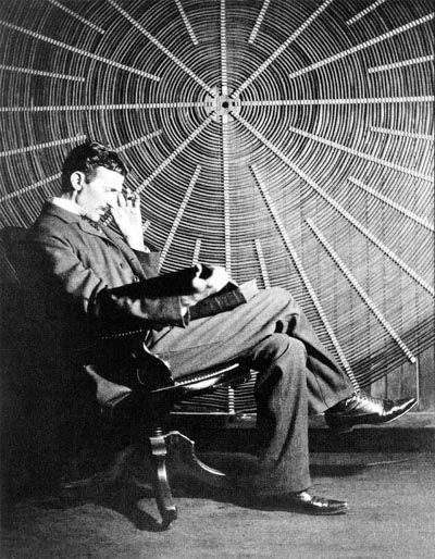 """Nikola Tesla, with Rudjer Boscovich's book """"Theoria Philosophiae Naturalis"""", in front of the spiral coil of his high-voltage transformer at East Houston St., New York"""