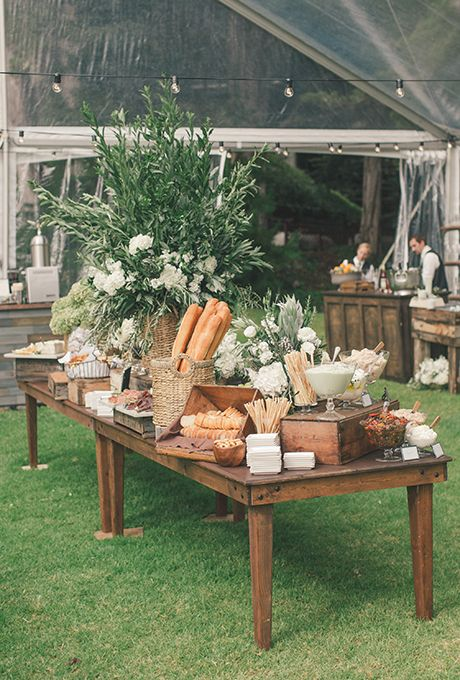 Brides.com: . A rustic bread, cheese, and charcuterie table decorated with a centerpiece of lush greenery and white peonies, created by Coastside Couture.:
