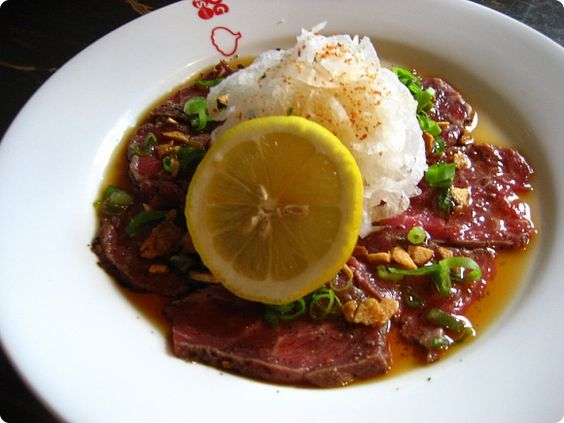 Seared beef sashimi with ponzu sauce topped with garlic chips and ...