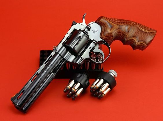 """Custom Colt Python  A member of Colt's famous and highly collectable """"Snake"""" series of revolvers, the Python was chambered in .357 Magnum. I say custom again because the grips are not factory stock. Note the speed loaders; a quick and efficient way to reload a revolver, mostly used in competition shooting. On a side note, you can tell the barrel length by the number of ribs/vents placed along the top. 2 ribs = 4 inches, 3 ribs = 6 inches and 4 ribs = 8 inches.  Why mention that?"""