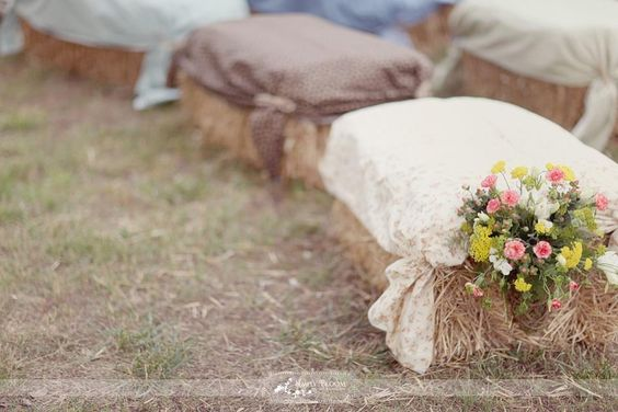 I love this cute alternative seating idea; bales of hay covered with vintage sheets and a colorful bouquet of flowers!