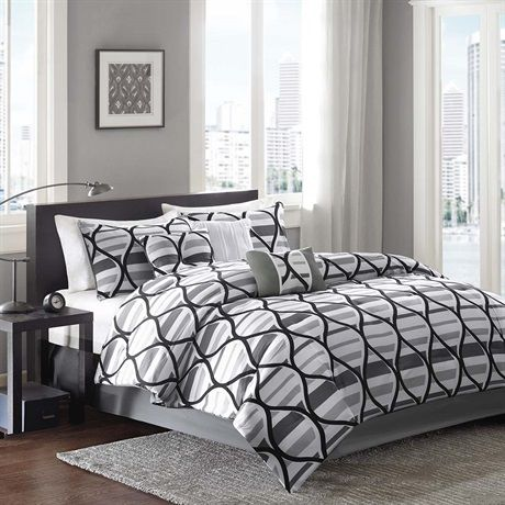 If you love geometric designs then the Double Infinity 7 Piece Comforter Set is just what you're looking for! The plush comforter features horizontal stripes in white and grey with an oversized fretwork design in black printed on microfiber over the top of the stripes. The two king shams feature the same stripe and fretwork design with a grey border. Three geometric decorative pillows in colors of grey and white add character to this look. A solid khaki bed skirt is also included to finish…