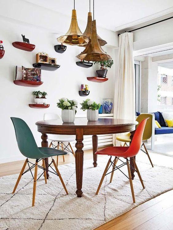 Música no décor Para os apaixonados por música, essa sala de jantar nada discreta, é uma ótima inspiração. Esse é o ambiente da foto, que pertence a um apartamento em Madri, onde os pendentes em formato de gramofone garantem o toque divertido ao cômodo, enquanto as cadeiras coloridas completam o visual. (Foto: Reprodução/Divulgação) #saladejantar #diningroom #chandelier #decoração #casavogue