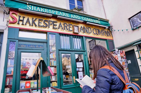 A woman reads a book outside Shakespeare and Company bookstore in Paris