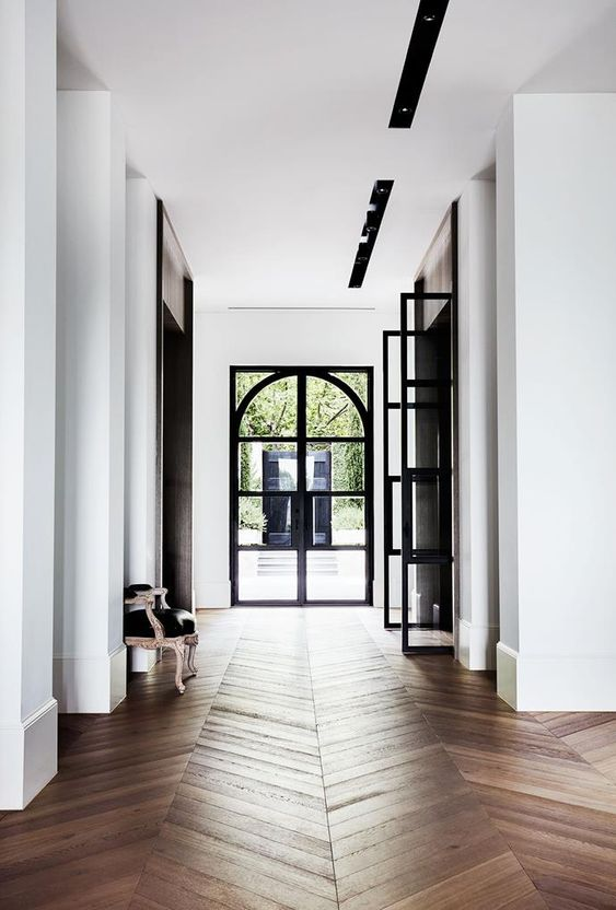 White walls, white ceiling with beautiful wood herringbone floors and black trim details