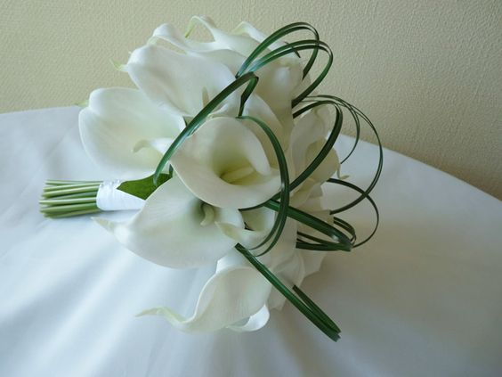 A modern, hand-tied bouquet of calla lilies with looped bear grass. The handle is bound in white ribbon with pearl pin decoration.