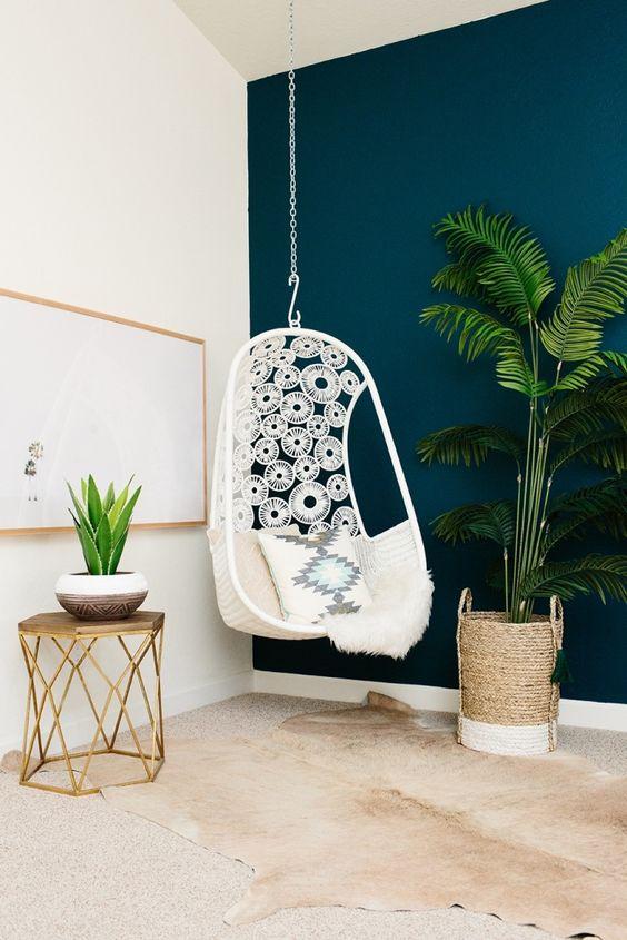 idée deco boheme chic avec pan de mur en peinture bleu canard, intérieur moderne avec chaise ouef et petite table à design origami en or