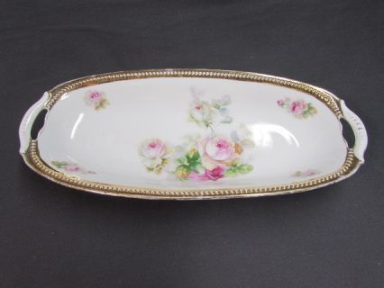 """Vintage PK Silesia Celery Dish.  This porcelain celery or relish dish was made between 1914 and 1918 by PK Silesia.  The tray features pale pink and yellow hued roses with green foliage.  The rim of the dish is beaded and gold gilt.  The dish has 2 handles.  It is approx. 12 1/4"""" x 5 3/4""""  x 1 5/8"""". There are no chips or cracks.  There is wear to the design and significant wear to the gold."""