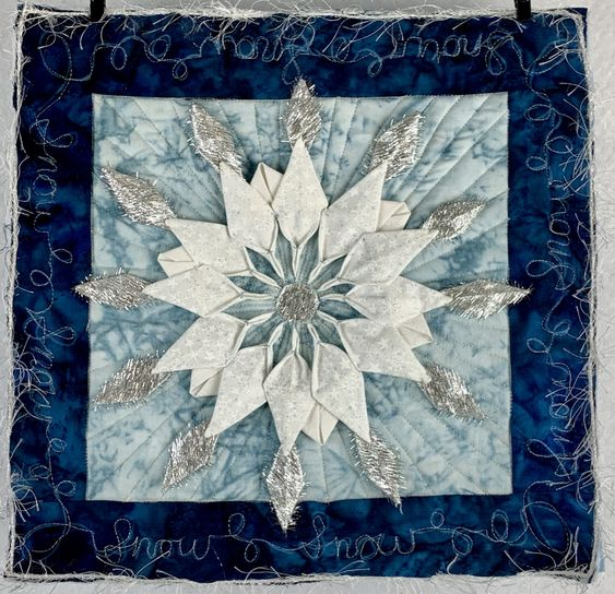 """A smaller quilt  measuring 10""""x10"""". 3D petals sewn into a fabric background and more petals added in a crazy fringy metallic fabric.  I love this technique."""