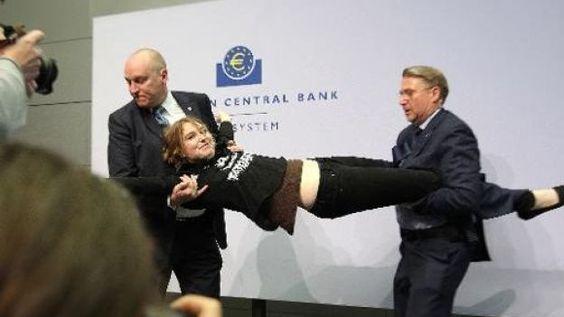 """La femme âgée d'une vingtaine d'années, qui s'était mêlée au public de journalistes présents, a grimpé sur la table devant M. Draghi en scandant an anglais """"arrêtez la dictature de la BCE"""" (""""end the ECB dictatorship""""), un slogan qu'elle arborait aussi sur son t-shirt, tout en lançant des confettis."""