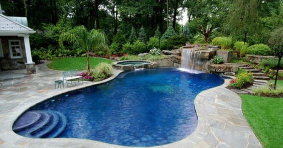 Back yard pool with a beautiful waterfall feature - i love all the greenery