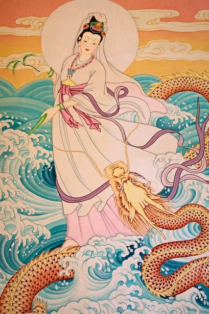 Mural adorning the walls of an outdoor temple in the heart of Chinatown, Bangkok.    Guanyin has a willow branch in one hand displaying her gentle nature and a vase pouring healing nectar in the other hand.  She rides the back of a dragon on ocean waves with confidence and command.  She is known as the one who hears the cries of the world.