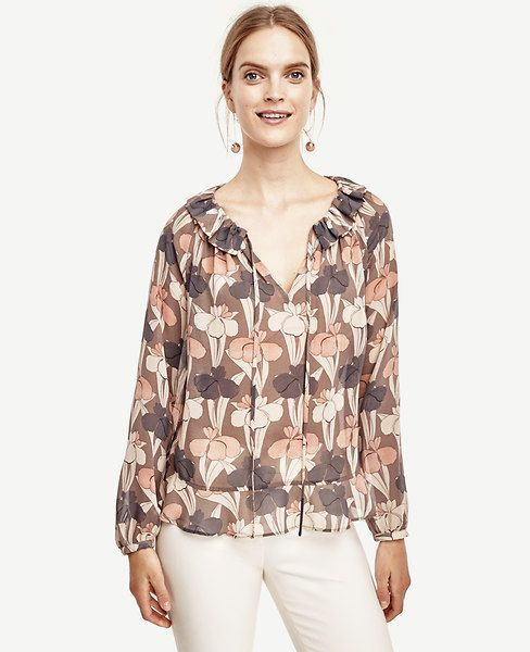 "Dressed in feminine florals, this peasant style blouse features a shirred ruffle neckline and slim tie neck for a look that's breezy and tailored - all at once. Split neck with ties and shirred ruffle collar. Long raglan sleeves with shirred cuffs and button closure. Peplum hem. 24"" long."