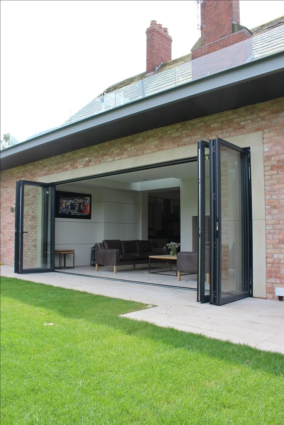 rear single storey brick extension with sandstone lintels bifolding doors and a steel framed overhang roof terrace above