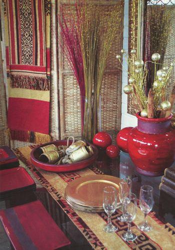 Decoración vibrante y energética: Rojo y dorado en una mezcla étnica y juvenil. Se trata de una mesa cuadrada, dispuesta como bufé, donde la cerámica pintada roja comparte protagonismo con los platos y elementos decorativos dorados.