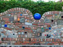 Gartenmauer im Hundertwasserstil, mit bunten Pflastersteinen im Format 7/9 sowie Pünktchen