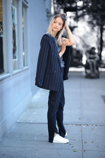 pinstripe suit jacket + slouchy trousers with side slits, worn with white sneakers + graphic tee: