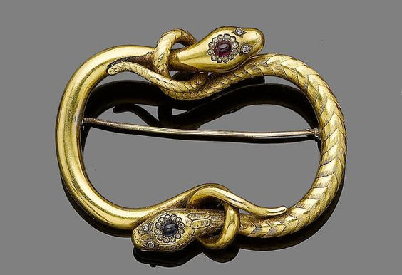 A serpent brooch, circa 1850. Modelled as two snakes, one head set with a cabochon ruby within an old brilliant-cut diamond surround with rose-cut diamond eyes, the other of textured finish and similar design set with a cabochon sapphire, each tail intertwined around the other's head to create a curved square outline, later pin fitting, length 6.5cm: