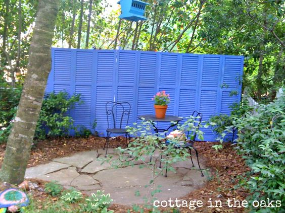 old shutters turned into privacy screen for a garden