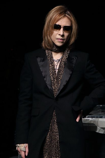 黒いロングコートにサングラスをかけて立っているXJAPAN・YOSHIKIの画像