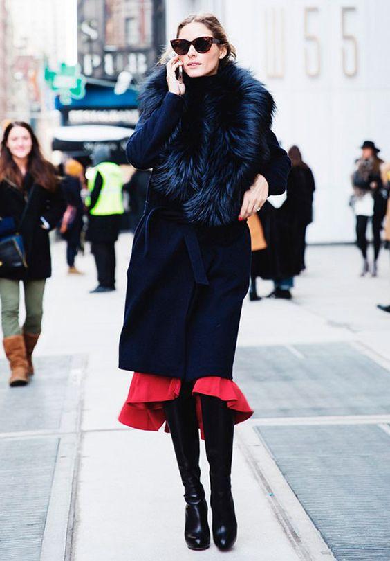 Street style look com saia vermelha, sobretudo preto e bota couro preta: