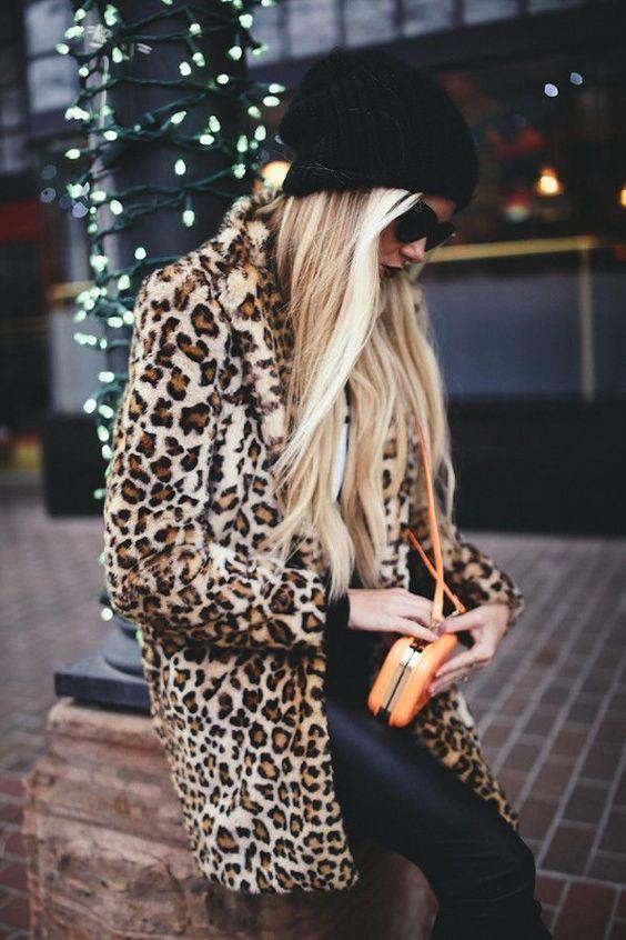 Perfecta combinación de estilo: Calzas negras, abrigo animal print, gorro de lana negro y anteojos. La cartera naranja le da el touch al Outfit: