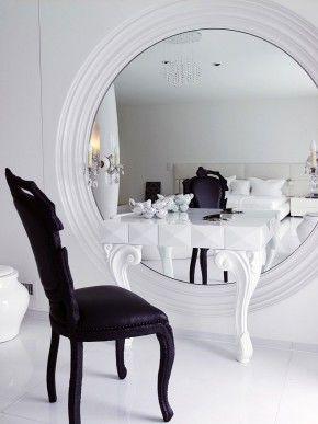 Fraaie make-up tafel. De zwarte stoel, de pootjes van de tafel en de omlijsting van de spiegel maken deze make-up tafel helemaal af. Maar het leukste van de hele opstelling is het effect van de tafel in de enorme spiegel. Zo krijg je een geweldig ruimtelijk effect dat in elke kamer past. Goed idee, briljant uitgevoerd. Ontworpen door Marcel Wanders. Marcel Wanders
