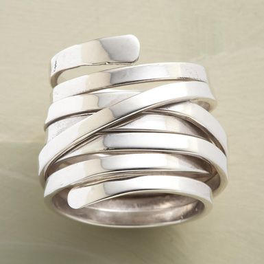A single length of sterling silver coils around the finger as randomly as a vine around a tree. Hammered surfaces mark the beginning and end points.