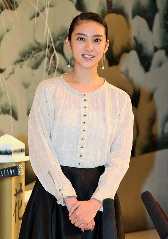 シンプルな服装で髪をまとめる武井咲