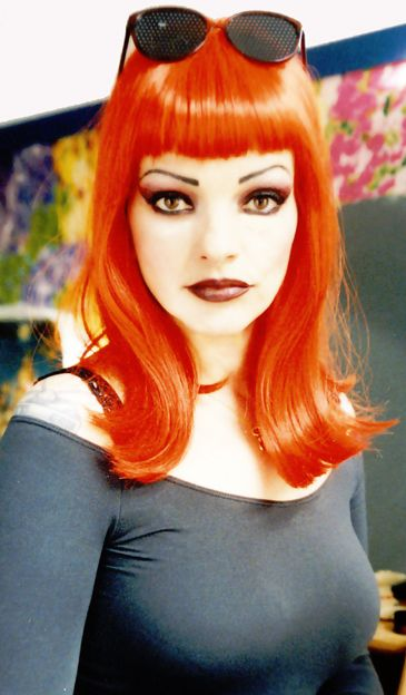 Nina Hagen with bright orange mid-length hair with blunt bangs.