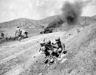 A Republic of Korea soldier, left, and an American officer search the pockets of a dead Communist soldier left behind by retreating Communist troops during U.S. Marines' counterattack against enemy in hills near Yongsan, Korea, on Sept. 4, 1950, in the Korean War. An enemy tank, one of several knocked out during battle, burns in the background. (AP Photo)
