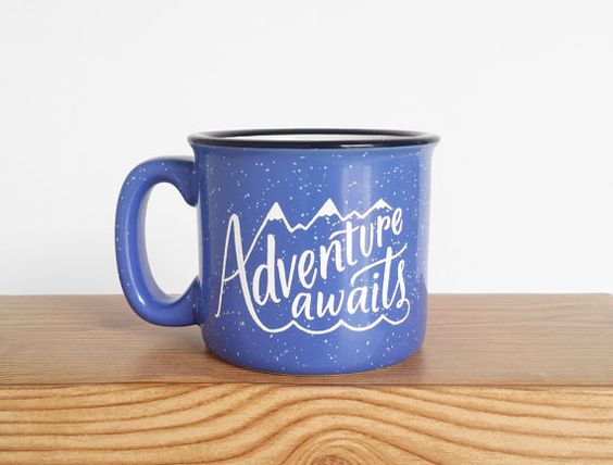 Adventure Awaits Campfire-style mug in a periwinkle blue with white lettering  This heavy ceramic 15 oz mug is perfect for the outdoor