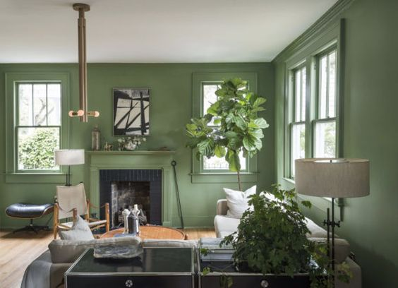 In the Charleston, South Carolina living room of Workstead founder Robert Highsmith, rich green walls are a nod to the lush botanicals of the city's historic downtown district. An original Kaare Klint Safari chair sits along custom pieces by Workstead, including the coffee table, floor lamps and a wooden pendant light.:
