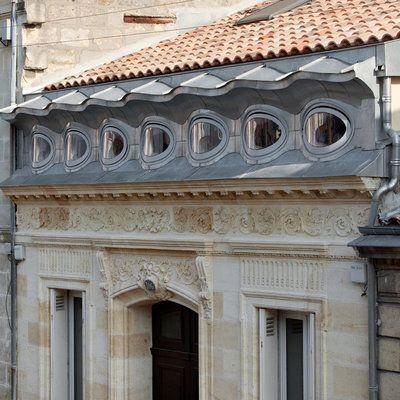 Le zinc dessine un passage entre les tuiles du toit et la pierre. La maison a reçu le Prix de la Surélévation Agora 2012.
