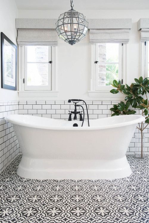 Stand alone bath tub with subway tiled walls and black and white patterned tile flooring   Lifestyle