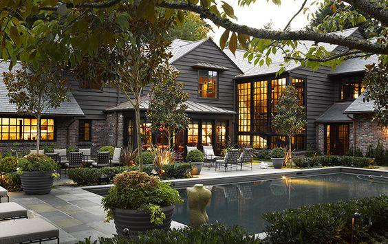 Murs de brique et de bardeaux de bois, toit d'ardoise… l'esprit « campagne » de la maison joue le contraste avec les grandes baies vitrées qui ouvrent sur la décoration intérieure luxueuse et scintillante.