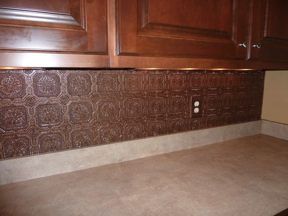 textured wallpaper backsplash painted with aged copper paint