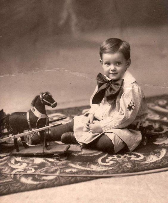 Little sailor boy, Earl Monnington Hopkins,  plays with a toy horse on wheels.
