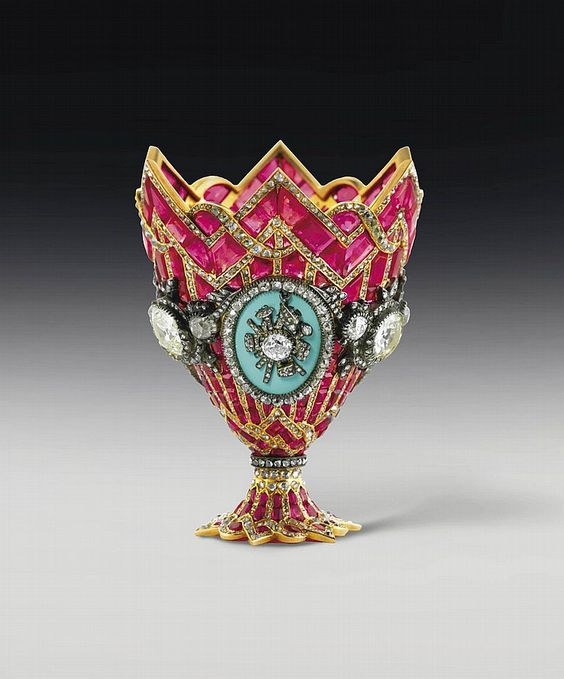 A MAGNIFICENT SWISS GOLD, RUBY, DIAMOND, AND ENAMEL ZARF <br />GENEVA, CIRCA 1840 <br />Of open-back construction, formed as chevrons and stripes of calibré-cut rubies between gold borders set with vari-cut diamonds, the mid-section set with three large old-mine-cut diamonds within vari-cut diamond garlands between three oval enamelled panels applied with vari-cut diamond and silver military trophies, two with Turkish crescent, the center of the base set with a ruby, <i>apparently ...